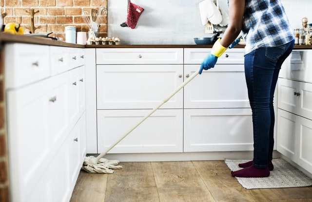 Person cleaning wooden floor in the kitchen