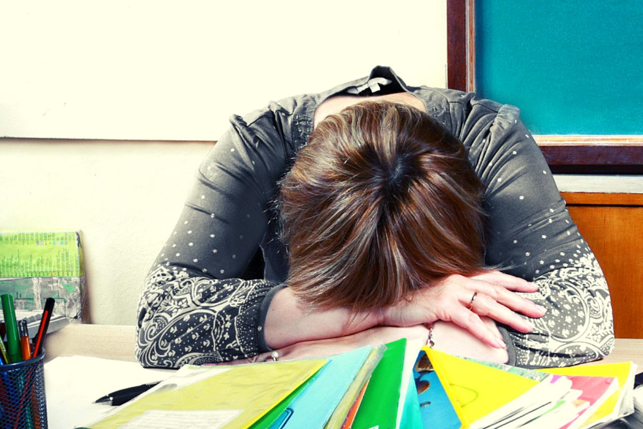 Teacher resting head on desk